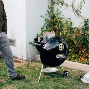 man next to barbecue grilling